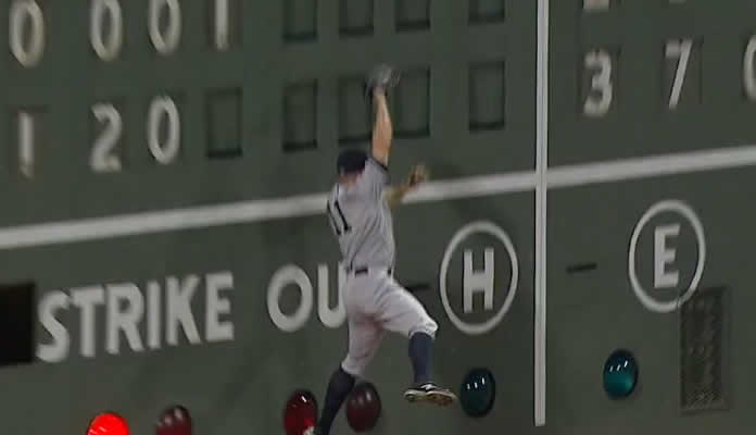 Brett Gardner drifts back on a deep line drive from David Ortiz and makes a leaping catch before slamming into the Green Monster on July 11, 2015