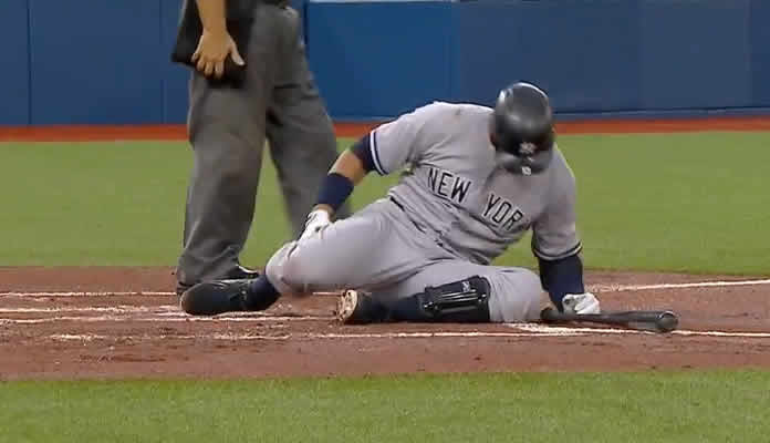 Alex Rodriguez falls to the ground after fouling a ball off his ankle and, after a short visit from trainers, stays in the game at Rogers Centre on September 21, 2015