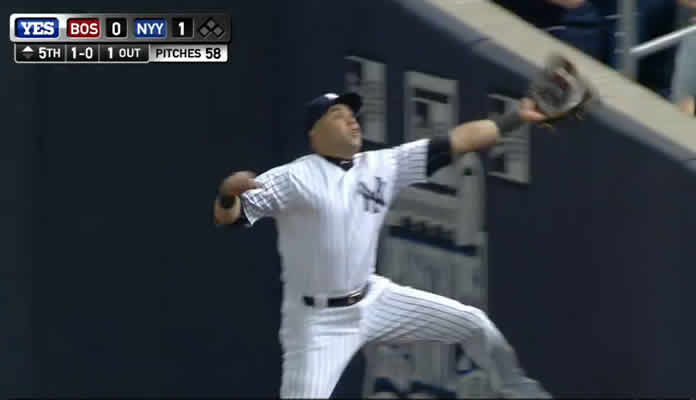 Carlos Beltran races into foul territory and makes a terrific leaping catch while crashing into the wall at Yankee Stadium on September 28, 2015